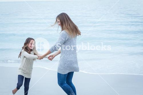 Mother and daughter playing at sea shore