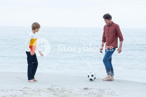 Father and son playing soccer at sea shore