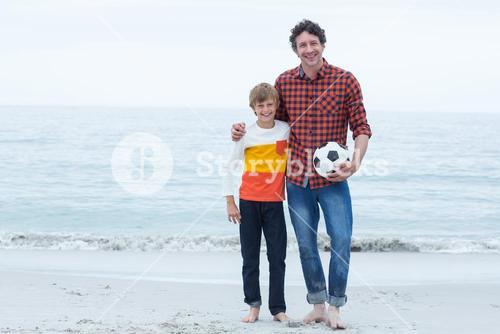 Father and son holding soccer ball at sea shore