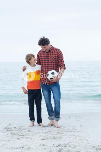 Father and son with soccer ball at sea shore