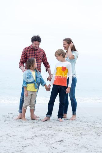 Children standing with parents at sea shore