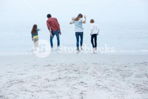 Family enjoying in shallow water at beach