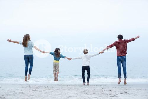 Family holding hands while jumping at sea shore