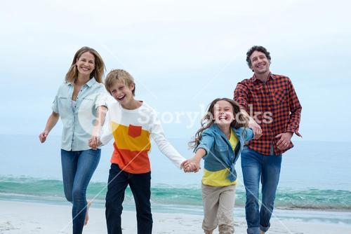 Family holding hands while running at sea shore