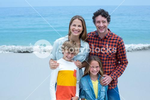 Cheerful parents with children standing on shore