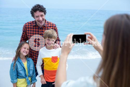 Mother photographing cheerful family