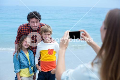 Family making faces while mother photographing with cellphone