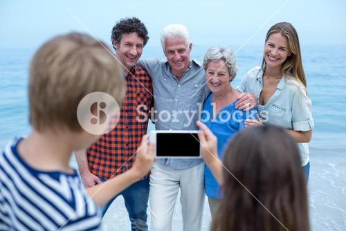 Siblings photographing family with mobile phone