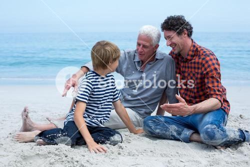 Multi-generation family resting at sea shore