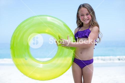 Cheerful girl holding inflatable ring at sea shore