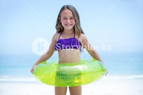 Cheerful girl with inflatable ring sea shore