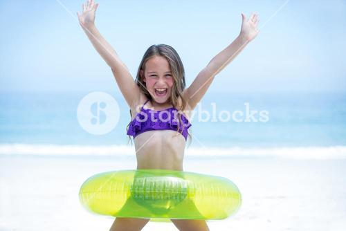 Girl with inflatable ring enjoying at sea shore