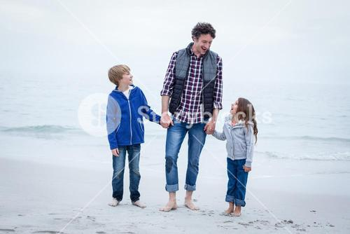 Cheerful father with children at sea shore