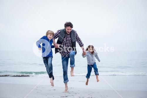 Family jumping at sea shore against clear sky