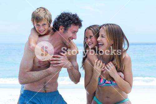 Cheerful parents with children at beach