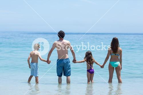 Family holding hands while standing in shallow water