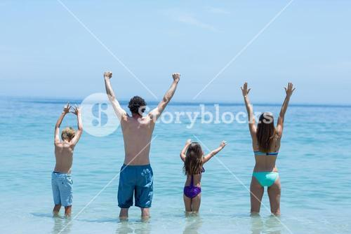 Family standing with arms raised in shallow water