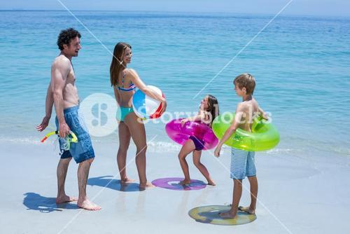 Family with swimming equipment at sea shore
