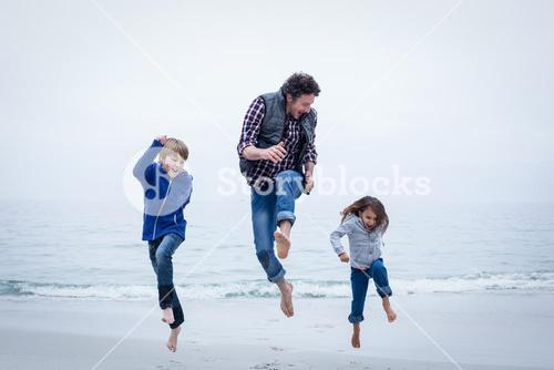 Cheerful family jumping at sea shore against clear sky