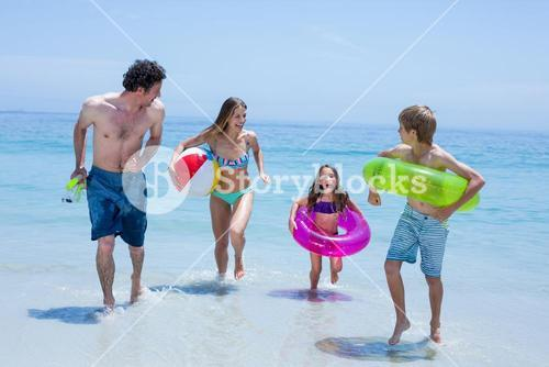 Cheerful family running in shallow water with swimming equipment