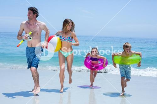 Cheerful family running with swimming equipment at sea shore