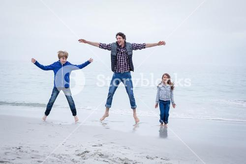 Father enjoying with children at sea shore