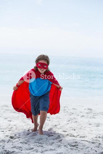Boy in superhero costume running while holding cape
