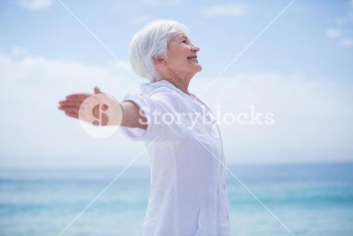 Senior woman smiling while exercising at beach