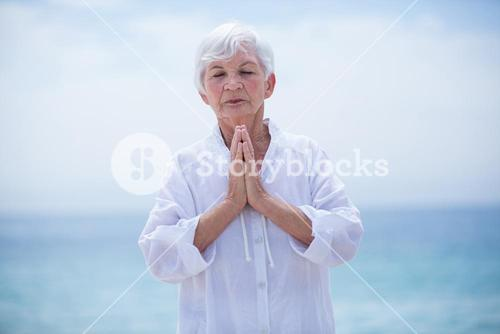 Senior woman with hands clasped