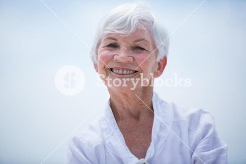 Portrait of smiling senior woman against sky