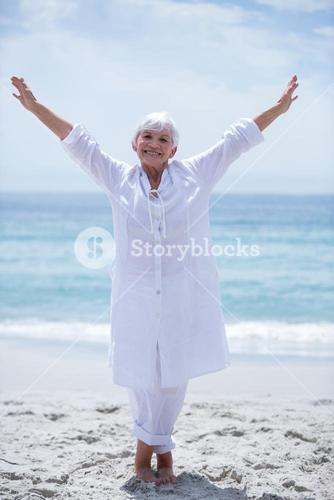 Cheerful senior woman with arms outstretched at sea shore