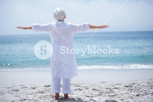 Senior woman exercising at sea shore on sunny day