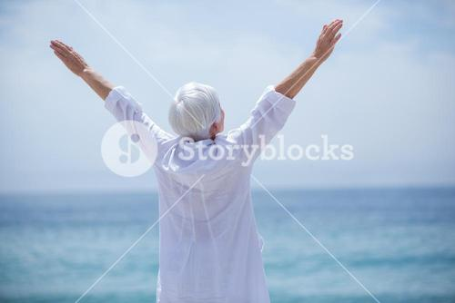 Senior woman exercising at beach on sunny day