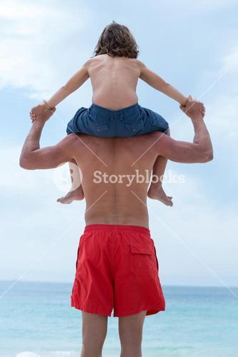 Rear view of man carrying son on shoulder