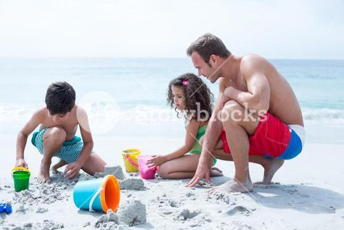 Father helping children building sand castle at beach