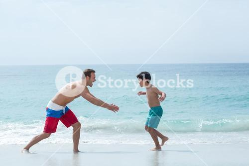 Father chasing son at beach
