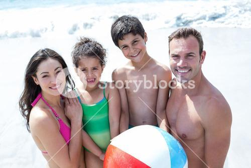 Smiling family with ball on sea shore at beach