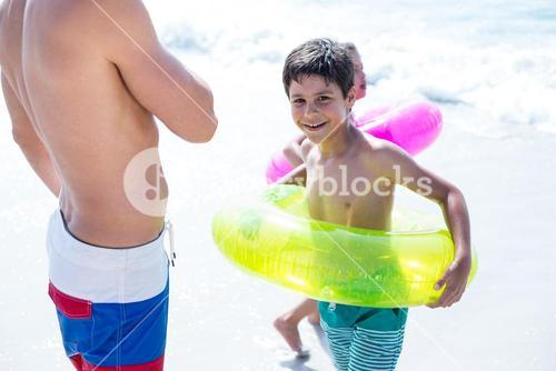 Children with swimming ring standing at beach