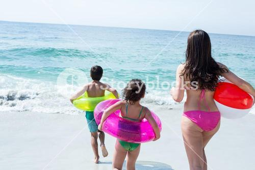 Mother with children holding swimming ring at beach