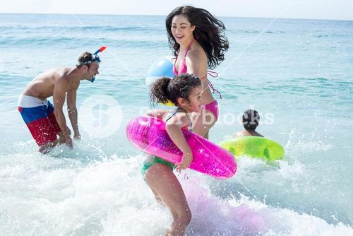 Family with swimming ring playing in sea