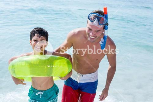 Happy family with swimming ring standing in sea