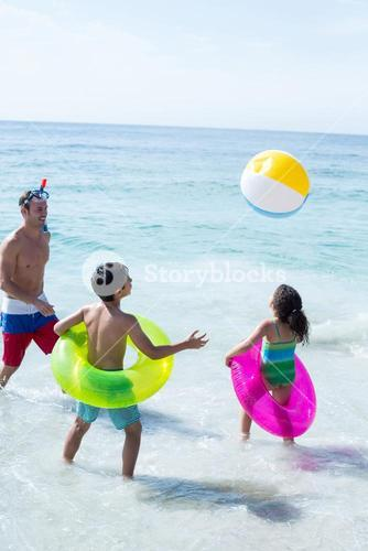 Father and children playing with ball on shore