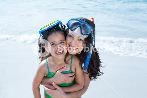 Mother and daughter wearing diving goggles at beach