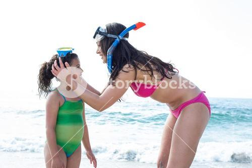 Mother wearing diving goggles to daughter at beach
