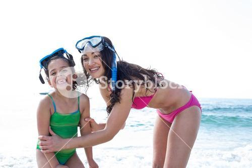 Mother and daughter with diving goggles at beach