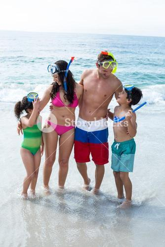 Family wearing diving goggles standing on sea shore