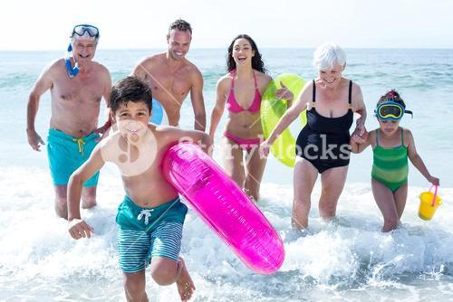 Multi-generation family running at beach