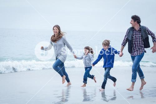 Cheerful family running at sea shore