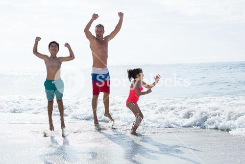 Children jumping with father at sea shore