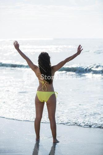 Woman in bikini standing with arms outstretched at sea shore